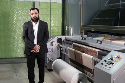 Muhammad Asif, CEO at Moti Fabrics, standing in front of one of the company's two Tiger-1800B MkII direct-to-textile printers © 2020 Mimaki