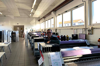 Filippo Taccani, founder and owner at Digitak, in the company's production department, surrounded by an arsenal of Mimaki's printing solutions. (c) 2020 Mimaki