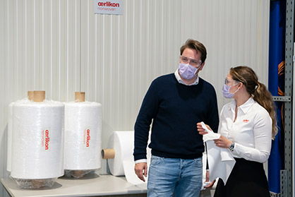 Oerlikon expert Juliane Müller-Weigel explains the benefits of an Oerlikon Nonwoven meltblown technology system to Philipp Heymann, CEO of Lindenpartner (Photo: Oerlikon)